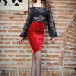 Charming young brunette womin black lace blouse, red skirt and high heels near brick wall. Sexy gorgeous young womnear old wall. Full length portrait of sensual womwith long curly hair — Foto de stock #40987643