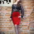 Charming young brunette womin black lace blouse, red skirt and high heels near brick wall. Sexy gorgeous young womnear old wall. Full length portrait of sensual womwith long curly hair — Stock fotografie #40987645