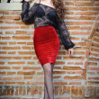 Charming young brunette womin black lace blouse, red skirt and high heels near brick wall. Sexy gorgeous young womnear old wall. Full length portrait of sensual womwith long curly hair — Stok Fotoğraf #40987647