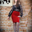 Charming young brunette womin black lace blouse, red skirt and high heels near brick wall. Sexy gorgeous young womnear old wall. Full length portrait of sensual womwith long curly hair — Stock fotografie #40987649