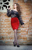 Charming young brunette woman in black lace blouse, red skirt and high heels near the brick wall. Sexy gorgeous young woman near old wall. Full length portrait of a sensual woman with long curly hair — Stock Photo