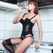 Attractive sexy red hair female with black lingerie and stockings drinking wine in a modern kitchen. Portrait of sensual redhead with black corset and long legs in modern scenery - indoor shot — Stock Photo