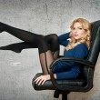 Attractive sexy blonde female with bright blue blouse and black stockings posing smiling sitting on office chair. Portrait of sensual fair hair woman with long legs on gray - studio shot — Stock Photo