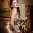 Young beautiful luxurious woman in elegant dress smiling holding a vintage telephone. Beautiful young woman in a luxurious classic interior. Seductive brunette woman in luxury manor, vintage style — Stock Photo #41283471
