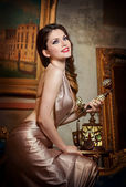 Young beautiful luxurious woman in elegant dress smiling holding a vintage telephone. Beautiful young woman in a luxurious classic interior. Seductive brunette woman in luxury manor, vintage style — Stock Photo