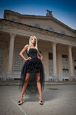 Beautiful woman in black dress posing outdoor. Sexy woman in stylish retro scene. Elegant woman in front of a castle. Portrait of woman in black elegant dress standing in front of an old building — Stock Photo