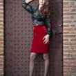 Charming young brunette womin black lace blouse, red skirt and high heels near brick wall. Sexy gorgeous young womnear old wall. Full length portrait of sensual womwith long curly hair — Stock fotografie #41522125