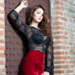 Charming young brunette woman in black lace blouse, red skirt and high heels near the brick wall. Sexy gorgeous young woman near old wall. Full length portrait of a sensual woman with long curly hair — Stock Photo #41522127