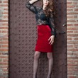 Charming young brunette woman in black lace blouse, red skirt and high heels near the brick wall. Sexy gorgeous young woman near old wall. Full length portrait of a sensual woman with long curly hair — Zdjęcie stockowe