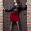 Charming young brunette womin black lace blouse, red skirt and high heels near brick wall. Sexy gorgeous young womnear old wall. Full length portrait of sensual womwith long curly hair — Stock fotografie #41522149