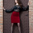 Charming young brunette womin black lace blouse, red skirt and high heels near brick wall. Sexy gorgeous young womnear old wall. Full length portrait of sensual womwith long curly hair — Stockfoto #41522149