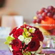 Beautiful bouquet of rose flowers, on table. Wedding bouquet of red roses. Elegant wedding bouquet on table at restaurant — Stock Photo