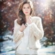 Portrait of young beautiful woman wearing white clothes outdoor. Beautiful brunette girl with long hair posing outdoor in a cold winter day. Beautiful fashionable young woman in winter scenery. — Stock Photo #41767395