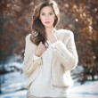 Portrait of young beautiful woman wearing white clothes outdoor. Beautiful brunette girl with long hair posing outdoor in a cold winter day. Beautiful fashionable young woman in winter scenery. — Stok fotoğraf #41767397