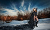 Lovely young lady posing dramatically with long black veil in winter scenery. Blonde woman with cloudy sky in background - outdoor shoot. Glamorous female in nature - gothic style — Stock Photo
