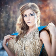 Lovely young lady in elegant dress posing winter scenery, royal look. Fashionable blonde woman with forest in background, outdoor shoot. Glamorous female with long fair hair in nature - princess style — Stok fotoğraf