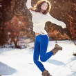 Attractive brunette girl with white sweater posing playing in winter scenery. Beautiful young woman with long hair enjoying the snow. Long legs young woman playing in wintertime outdoor — Stockfoto