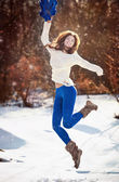 Attractive brunette girl with white sweater posing playing in winter scenery. Beautiful young woman with long hair enjoying the snow. Long legs young woman playing in wintertime outdoor — Stock Photo