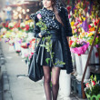 Beautiful brunette woman with gloves holding a rose in front of  florist shops. Fashionable female with head scarf at long legs at flower shop. Pretty brunette in black choosing flowers - urban shot — Stock Photo #41846979