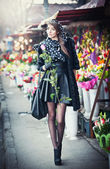 Beautiful brunette woman with gloves holding a rose in front of  florist shops. Fashionable female with head scarf at long legs at flower shop. Pretty brunette in black choosing flowers - urban shot — Stock Photo