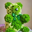 Wedding guest table set for an event. Green bear decoration on restaurant table. Teddy bear made by green flowers to decorate an elegant wedding table. — Stock Photo