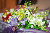 Beautiful bouquet of wild flowers, on table. Wedding bouquet of white an mauve flowers. Elegant wedding bouquet on table at restaurant. Floral arrangements on wedding ceremony detail. — Stock Photo