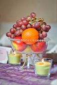 Wedding decorations with fruits arrangement and candles. Arrangement with grapes, orange and apples on wedding ceremony detail. Elegant and colorful wedding arrangement with fruits and candles — Stock Photo