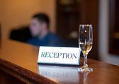 Příjem karet a šampaňské izolovaných na dřevěný stůl. Recepce s kartou a skla. Recepce deska. — Stock fotografie