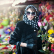 Beautiful brunette woman with gloves choosing flowers at the florist shop. Fashionable female with sunglasses and head scarf at flower shop. Pretty brunette in black choosing flowers - urban shot — Stock Photo #42222587