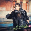 Beautiful brunette woman sitting outside in urban scene. Fashionable female with head scarf with a rose on her knees - outdoor shot. Woman in black sitting on a bench in the city — Stock Photo