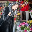 Beautiful brunette woman with gloves choosing flowers at the florist shop. Fashionable female with sunglasses and head scarf at flower shop. Pretty brunette in black choosing flowers - urban shot — Stock Photo #43112683