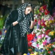 Beautiful brunette woman with gloves choosing flowers at the florist shop. Fashionable female with sunglasses and head scarf at flower shop. Pretty brunette in black choosing flowers - urban shot — Stock Photo #43112697