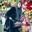 Beautiful brunette woman with gloves choosing flowers at the florist shop. Fashionable female with sunglasses and head scarf at flower shop. Pretty brunette in black choosing flowers - urban shot — Stock Photo #43112719