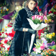 Beautiful brunette woman with gloves choosing flowers at the florist shop. Fashionable female with sunglasses and head scarf at flower shop. Pretty brunette in black choosing flowers - urban shot — Stock Photo #43112741