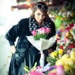 Beautiful brunette woman with gloves choosing flowers at the florist shop. Fashionable female with sunglasses and head scarf at flower shop. Pretty brunette in black choosing flowers - urban shot — Stock Photo #43112745