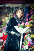 Beautiful brunette woman with gloves choosing flowers at the florist shop. Fashionable female with sunglasses and head scarf at flower shop. Pretty brunette in black choosing flowers - urban shot — Stock Photo