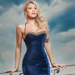 Fashion beautiful young woman in blue dress posing outdoor with cloudy dramatic sky in background. Sensual long hair blonde with tight-fitting elegant dress posing on ledge — Stock Photo #43595789