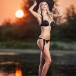 Portrait of young sexy blonde girl in bikini and big black hat at the beach in sunset. Sensual attractive woman in black swimsuit on beach. Caucasian woman with perfect body relaxing on the beach. — Stock Photo #43597285
