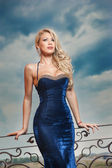 Fashion beautiful young woman in blue dress posing outdoor with cloudy dramatic sky in background. Sensual long hair blonde with tight-fitting elegant dress posing on ledge — Stock Photo