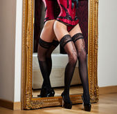 Attractive woman in red lingerie posing challenging near a large mirror. Sensual woman with long legs and high heels in corset. Classic boudoir shot. Erotic photo. — Stock Photo