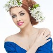 Portrait of beautiful girl in studio with spring flowers in her hair. Sexy young woman in blue with bright white flowers. Creative hairstyle and makeup, fashion photo studio shot — Stock fotografie