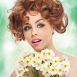 Portrait of beautiful curly girl in studio with daffodils. Sexy young woman with beautiful blue eyes with bright white flowers. Creative hairstyle and makeup, fashion photo studio shot — Stock Photo #44495003