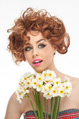 Portrait of beautiful curly girl in studio with daffodils. Sexy young woman with beautiful blue eyes with bright white flowers. Creative hairstyle and makeup, fashion photo studio shot — Stock Photo