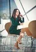 Fashion attractive girl in dark green dress sitting on chair writing, indoor shot. Modern urban scenery. Fashion art photo of sensual lady in glass and steel scenery. Girl with high heels at table — Stock Photo