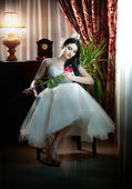 Young beautiful luxurious bride sitting holding a red rose in classic scenery. Attractive bride with curtains and lamp in background. Seductive brunette with ribbon in luxury manor, vintage style — Stock Photo
