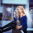 Attractive sexy blonde female with bright blue blouse and black stockings posing smiling holding a glass with red wine. Portrait of sensual fair hair woman with long legs in modern kitchen — Stock Photo #44624789