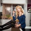 Attractive sexy blonde female with bright blue blouse and black stockings posing smiling holding a glass with red wine. Portrait of sensual fair hair woman with long legs in modern kitchen — Stock Photo #44624795