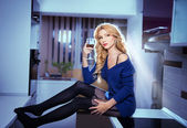 Attractive sexy blonde female with bright blue blouse and black stockings posing smiling holding a glass with red wine. Portrait of sensual fair hair woman with long legs in modern kitchen — Stock Photo