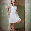 Beautiful girl posing fashion near an old wall. Pretty young woman posing laying on a wall. Very attractive blonde girl with a transparent white short dress. Romantic young woman posing — Stock Photo