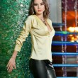 Attractive brunette woman with long hair in elegant yellow blouse and black leather pants standing near bright green wall in a nightclub. Gorgeous model posing in a modern emerald textured scenery — Stock Photo
